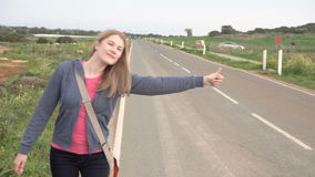 Young happy woman walking by a countryside road hitchhiking. Looking for a ride to start a journey. Young happy woman walking by a countryside road hitchhiking stock footage