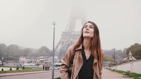 Young happy woman walking near the Eiffel tower in Paris, France. Tourist looking around and smiling. Slow motion. Traveling female enjoying the beautiful stock footage