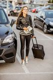 Woman renting a car. Young and happy woman walking with suitcase holding rental contract on the car parking Stock Images