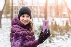 Young happy woman in warm purple dawn jacket smiling while making selfie with smartphone during walk in winter city park. Pretty. Girl enjoys winter vacations royalty free stock photo