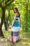 Young happy woman wearing long dress walking in green park stock photos