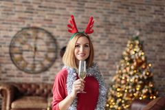Young happy woman wearing red dress with antler deer headband holding champagne glass while smiling at camera. Royalty Free Stock Images