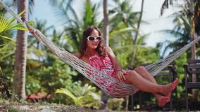 Young happy woman wearing sunglasses laying at hammock relaxing enjoying vacation. 1920x1080 stock footage