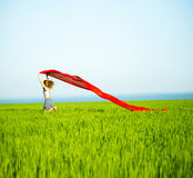 Young happy woman in wheat field with fabric Stock Photography