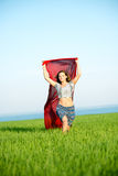 Young happy woman in wheat field with fabric Royalty Free Stock Image
