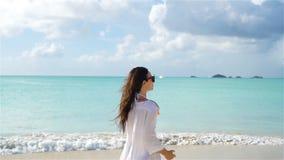 Young beautiful woman having fun on tropical seashore. Happy girl walking at white sand tropical beach. Young happy woman on white beach walking stock video