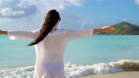 Young beautiful woman having fun on tropical seashore. Happy girl walking at white sand tropical beach. SLOW MOTION. Young happy woman on white beach walking stock footage