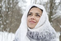 The young happy woman in a white knitted scarf lau Royalty Free Stock Photos
