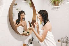 Young happy woman in white towel brushing teeth and looking at smartphone in bathroom with mirror. Slim woman with natural. Skin and wet hair daily routine royalty free stock photography