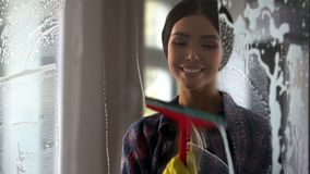 Young happy woman wiping glass surface after spray, cleaning service quality. Stock footage Stock Photography