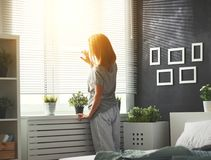 Young   woman woke up in the morning in the bedroom by the windo Stock Photography