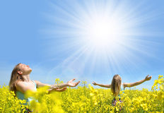 Young happy womans on blooming rapeseed field Stock Photo