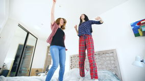 Young happy women couple dancing over a bed with earphones and have fun in bedroom at home stock video