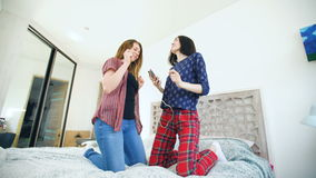 Young happy women couple dancing over a bed with earphones and have fun in bedroom at home stock footage