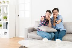 Young happy women friends watching tv together. Young happy women friends sitting on living room sofa at home watching tv together and looking at comedy program Royalty Free Stock Photo