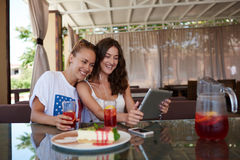 Young happy women having video conference on touch pad while sitting in modern cafe in summer day, Royalty Free Stock Photography