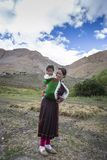 Indian woman carrying baby on her back in spiti valley Stock Photos
