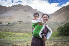 Indian woman carrying baby on her back in spiti valley Royalty Free Stock Images