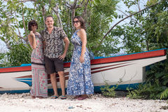 Young happy women and man posing near old ship at tropical white sand beach. Bali, Indonesia. royalty free stock image