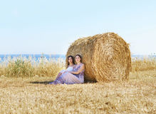 Young and happy women in a meadow of rye Stock Images