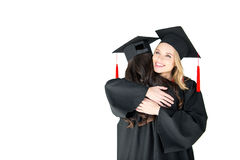 Young happy women in mortarboards hugging on white background Royalty Free Stock Images