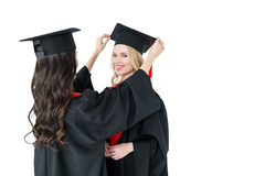 Young happy women in mortarboards standing together on white background Stock Images