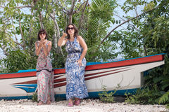 Young happy women posing near old ship at tropical white sand beach. Bali, Indonesia. Stock Image