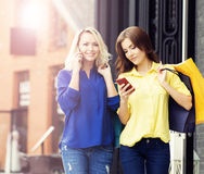Young and happy women with shopping bags in the city Royalty Free Stock Images