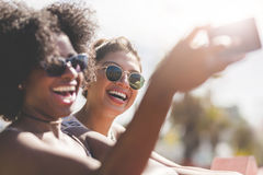 Young happy women taking themselves photo by mobile stock photo