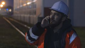 Young and happy worker in hard helmet talking by phone at night. 4k stock video footage