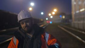 Smiling worker at hignt. He is in hard helmet and reflective jacket. 4k stock video footage