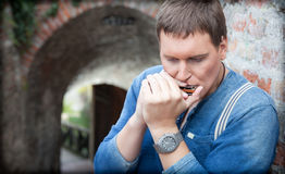 Young harmonica player plays on the street Royalty Free Stock Images