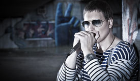 Young harmonica player plays on the street Stock Photography