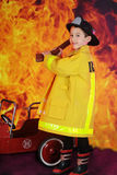 Young Hatchet Weilding Fireman. A young `fire fighter` happily weilding a hatchet before a big blaze Royalty Free Stock Images