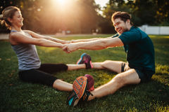 Young health couple doing stretching exercise Royalty Free Stock Images