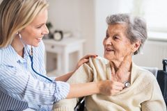 A health visitor examining a senior woman with a stethoscope at home. A young health visitor examining a senior women with a stethoscope at home stock photo