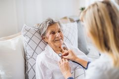 A health visitor examining a sick senior woman lying in bed at home with stethoscope. A young health visitor examining a sick senior women lying in bed at home royalty free stock photos