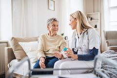 A health visitor explaining a senior woman how to take pills. A young health visitor explaining a senior women how to take medicine and pills royalty free stock photography