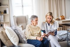 A health visitor explaining a senior woman how to take pills. A young health visitor explaining a senior women how to take medicine and pills royalty free stock photo