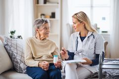 A health visitor explaining a senior woman how to take pills. A young health visitor explaining a senior women how to take medicine and pills royalty free stock images