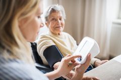 A health visitor measuring a blood pressure of a senior woman at home. A young health visitor measuring a blood pressure of a senior women in wheelchair at home royalty free stock photography