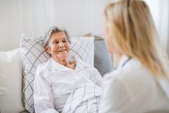 A health visitor talking to a sick senior woman lying in bed at home. A young health visitor talking to a happy sick senior women lying in bed at home stock image