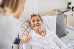 A health visitor talking to a sick senior woman lying in bed at home. A young health visitor talking to a happy sick senior women lying in bed at home royalty free stock photos