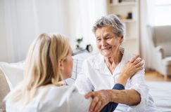 A health visitor talking to a sick senior woman sitting on bed at home. A young health visitor talking to a happy sick senior women sitting on bed at home stock photo