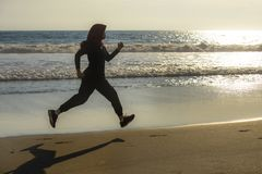 Young healthy and active runner Muslim woman in Islam hijab head scarf running and jogging on the beach wearing traditional arab. Sport clothes in fitness stock photo