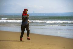 Young healthy and active runner Muslim woman in Islam hijab head scarf running and jogging on the beach wearing traditional arab. Sport clothes in fitness royalty free stock image