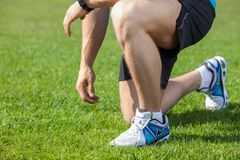 Young healthy athlete has his shoelaces untied Royalty Free Stock Photography