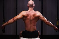 Young healthy bald ripped man with big muscles posing in gym, vi royalty free stock images