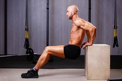 Young healthy bald ripped man with big muscles pushing up in gym royalty free stock photos