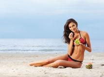 A young brunette woman in a swimsuit eating grapes Stock Photography